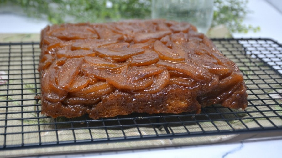 Side shot of caramel apple upside down cake on a rack.