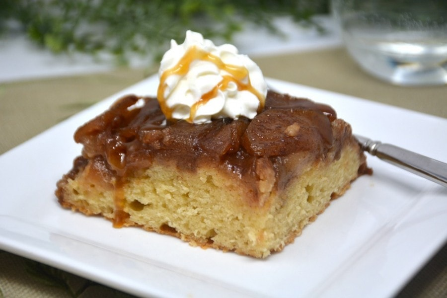 Slice of caramel apple cake with whipped cream on a white plate.