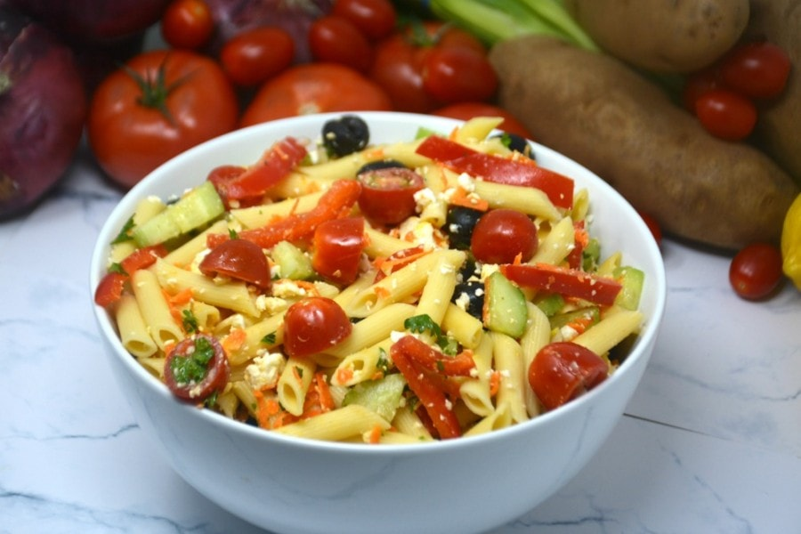 Greek pasta salad recipe in a white bowl with vegetables in the background.