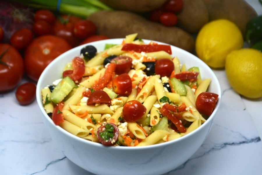 Picture of Greek pasta salad with lemons, tomatoes and other vegetables in the background.