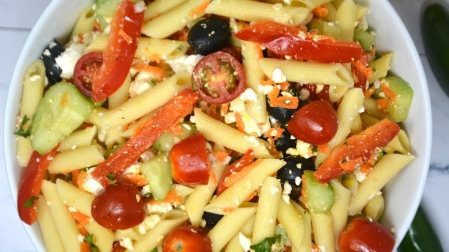 Overhead closeup of Greek pasta salad recipe in a white bowl.