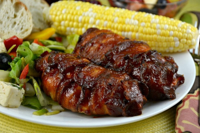 Barbecue Chicken on a white plate with corn on a yellow placemat.