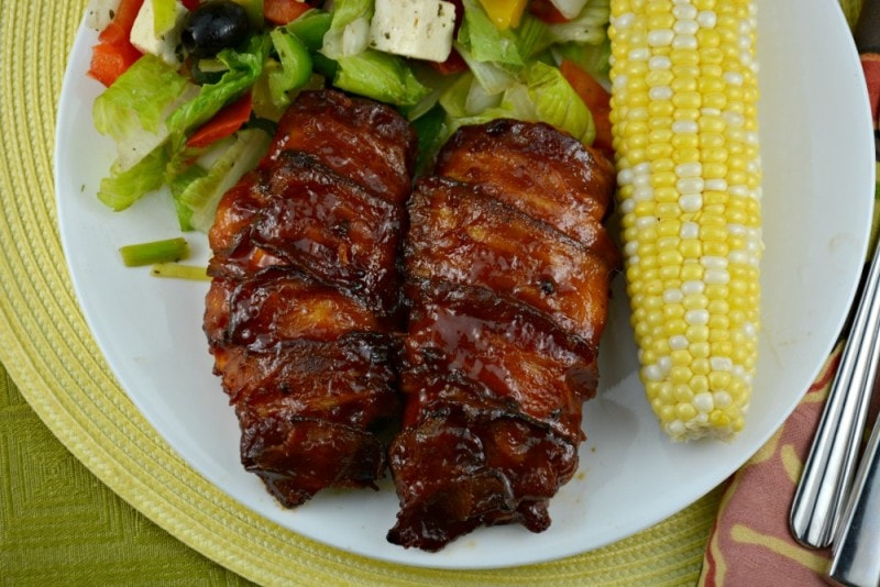 Two pieces of Bacon Wrapped Barbecue Chicken on a white plate with corn.