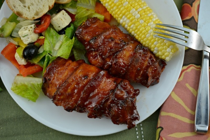 Overhead shot of Bacon Wrapped Barbecue Chicken on a green placemat.