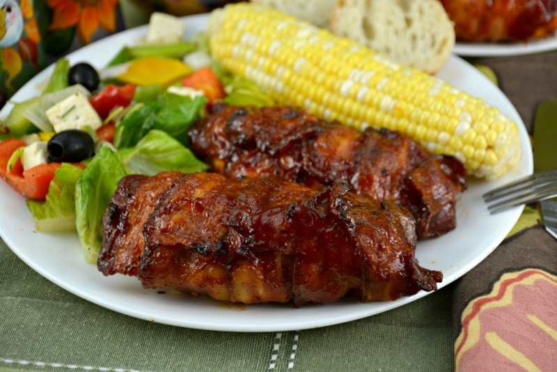 Bacon Wrapped Barbecue Chicken close up with salad and corn in background.