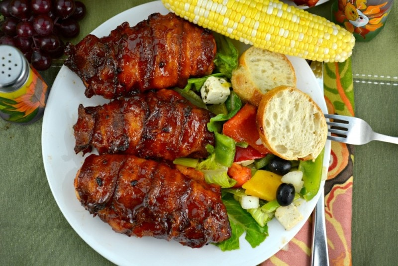 3 pieces of Bacon Wrapped Barbecue Chicken on a plate with salad and corn on the cob.