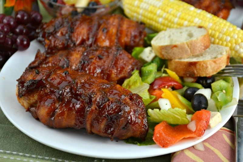 Bacon Wrapped Barbecue Chicken on a white plate with salad and bread.