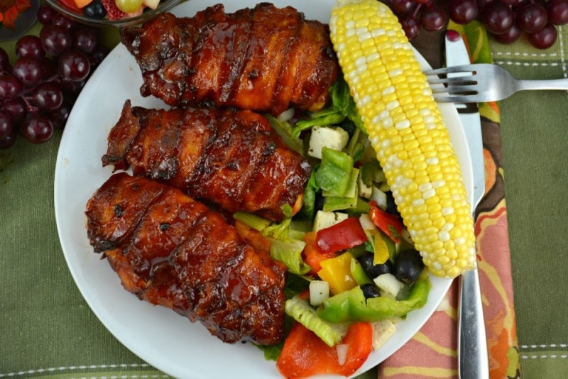 Bacon Wrapped Barbecue Chicken on a plate with salad, corn and a fork on a green placemat with an orange napkin.