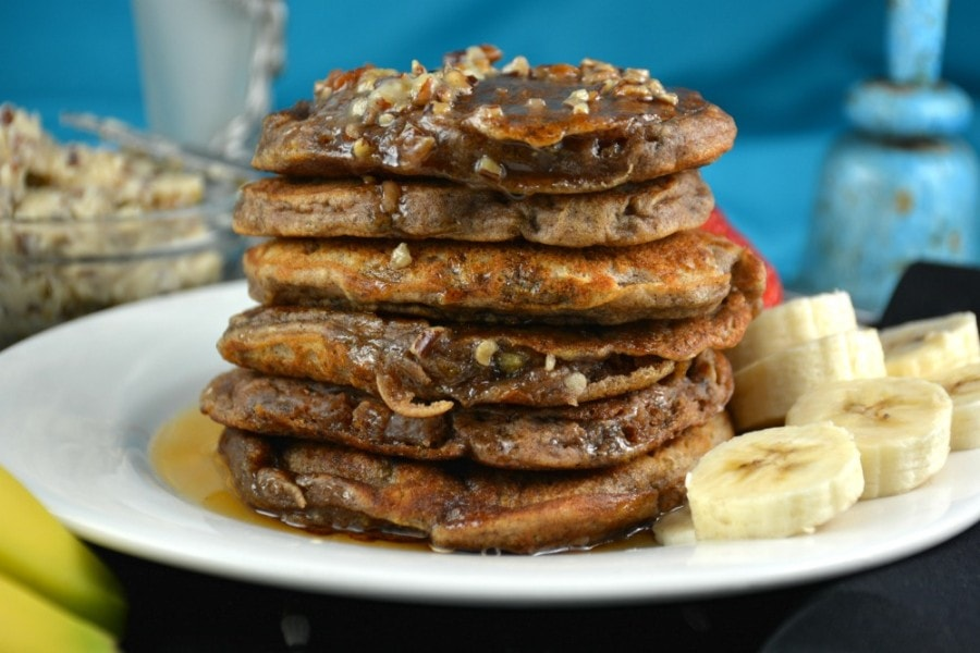 Stack of banana pancakes with pecan butter and some sliced bananas on the side.
