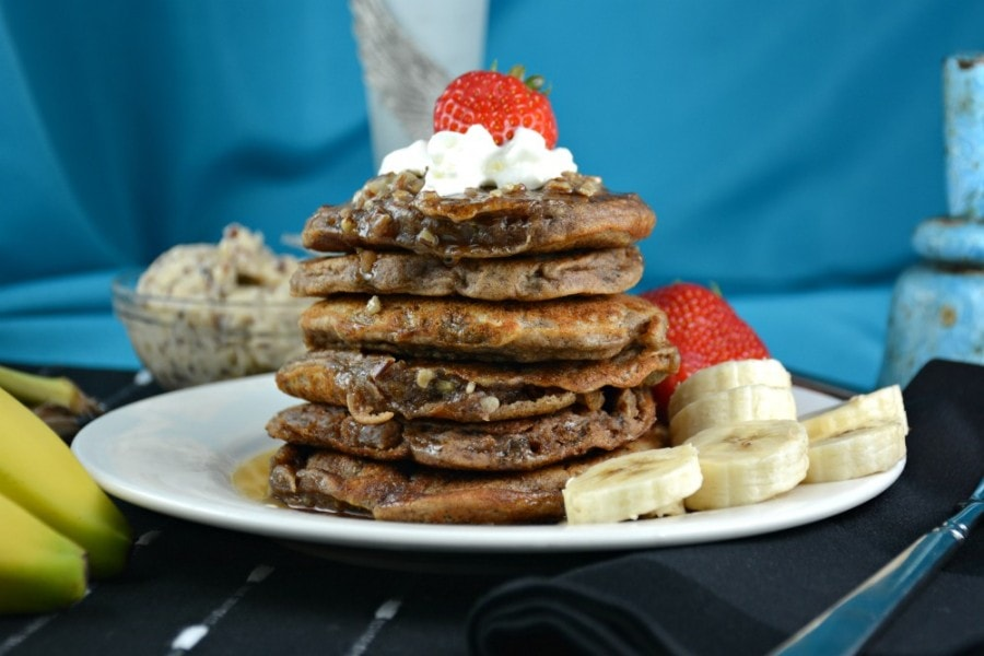Six Banana Hotcakes stacked on a white plate with sliced bananas, strawberries and whipped cream covered in Pecan Butter.