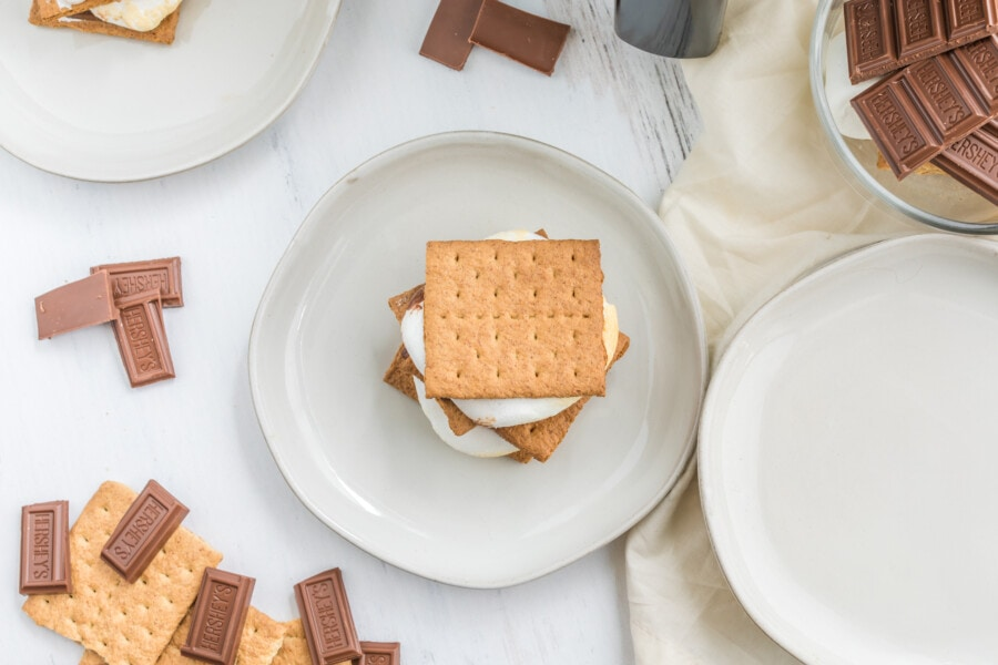 Overhead shot of air fryer s'mores on white plate with more plates and ingredients surrounding it