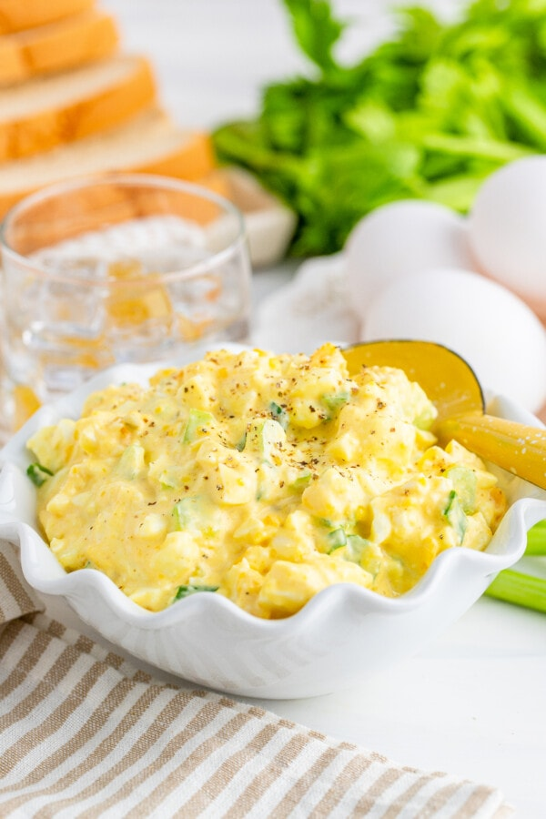 Egg salad with spoon in white bowl with glass, bread, and more eggs in background