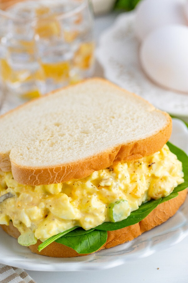 Closeup shot of egg salad sandwich on white plate