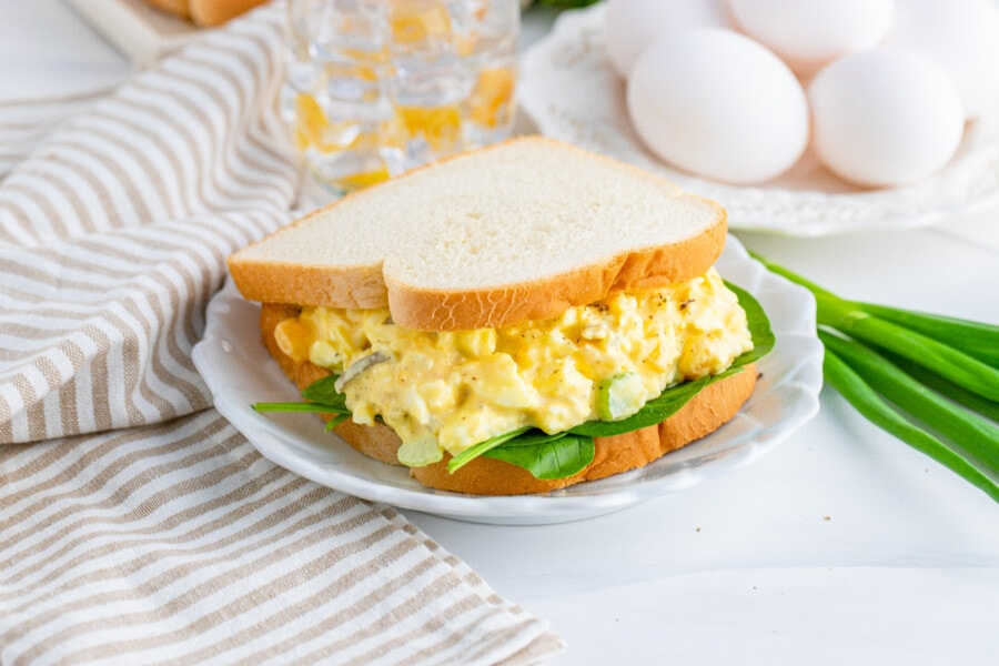 Classic egg salad sandwich on white plate with eggs on plate in background