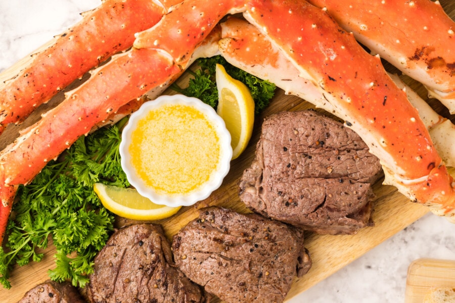 overhead shot of cooked steak and crab legs with melted buttery dipping sauce in the middle