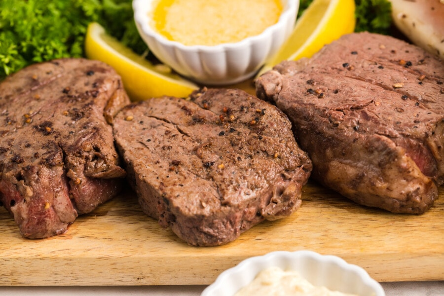 three filet mignon morsels cooked to perfection sitting on a cutting board waiting to be served