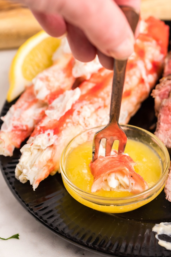 delicious-looking cooked crab meat on a fork being dipped in butter