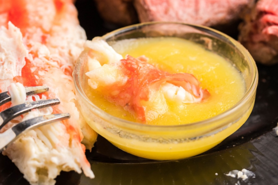 a piece of crab meat in melted butter sauce with a fork poised to grab the bite