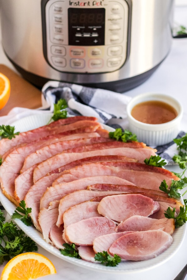 A platter of a completed Instant Pot ham recipe sitting in front of a pressure cooker