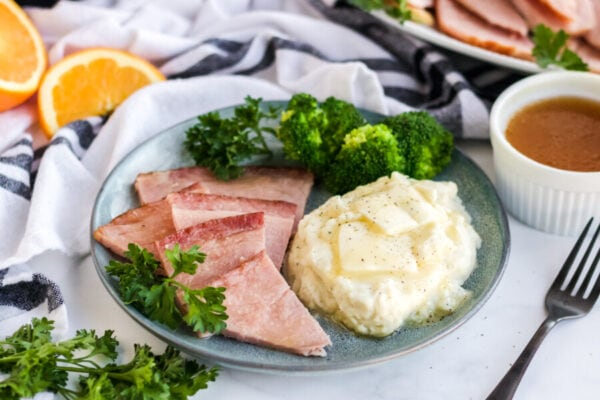 instant pot scalloped potatoes and ham served on a plate with a side of broccoli