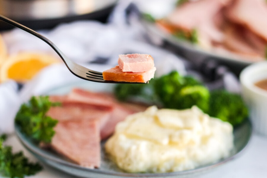 Instant Pot ham on a fork in focus with a plate of instant pot scalloped potatoes and ham blurry in the background