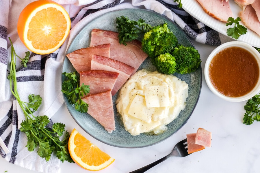 Overhead shot of sliced ham with mashed potatoes on plate