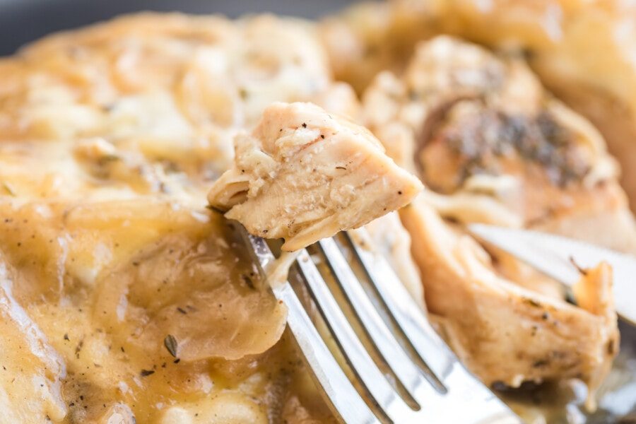 Closeup of fork taking a piece of French onion chicken bake