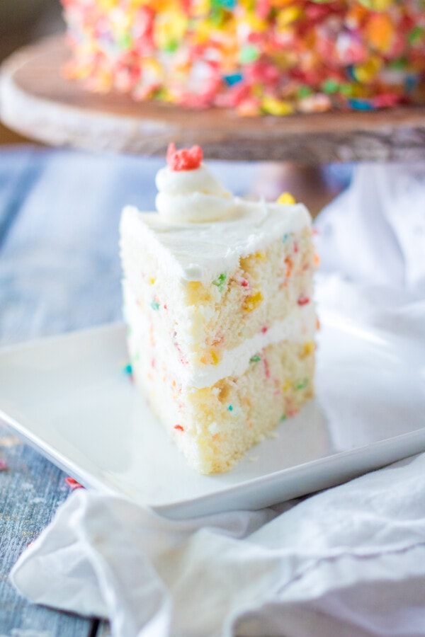 Slice of Fruity Pebble cake on white plate with whole cake in background
