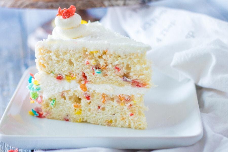 Closeup shot of slice of Fruity Pebble cake on whaite plate.