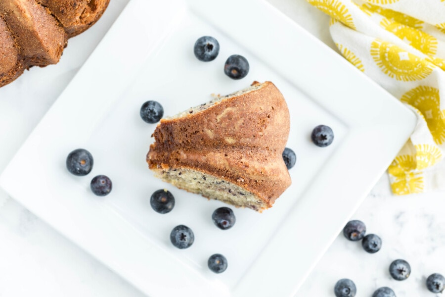 Overhead shot of a slice of lemon blueberry bundt cake with fresh blueberries scattered on the plate and table