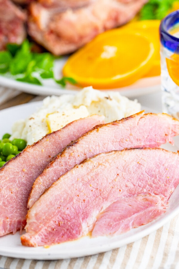 Closeup shot of sliced ham with mashed potatoes and green beans on white plate