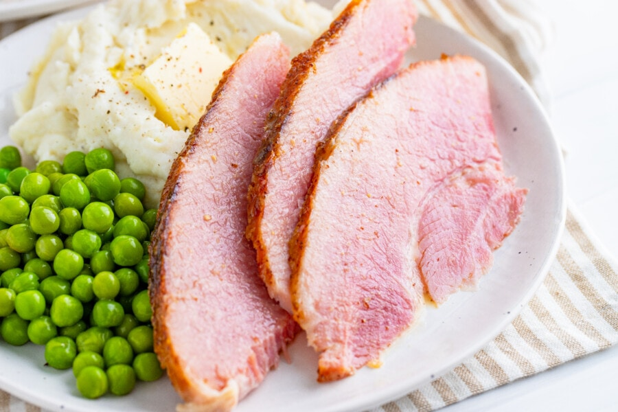 Closeup shot of sliced ham with honey mustard sauce for ham with mashed potatoes and peas on white plate