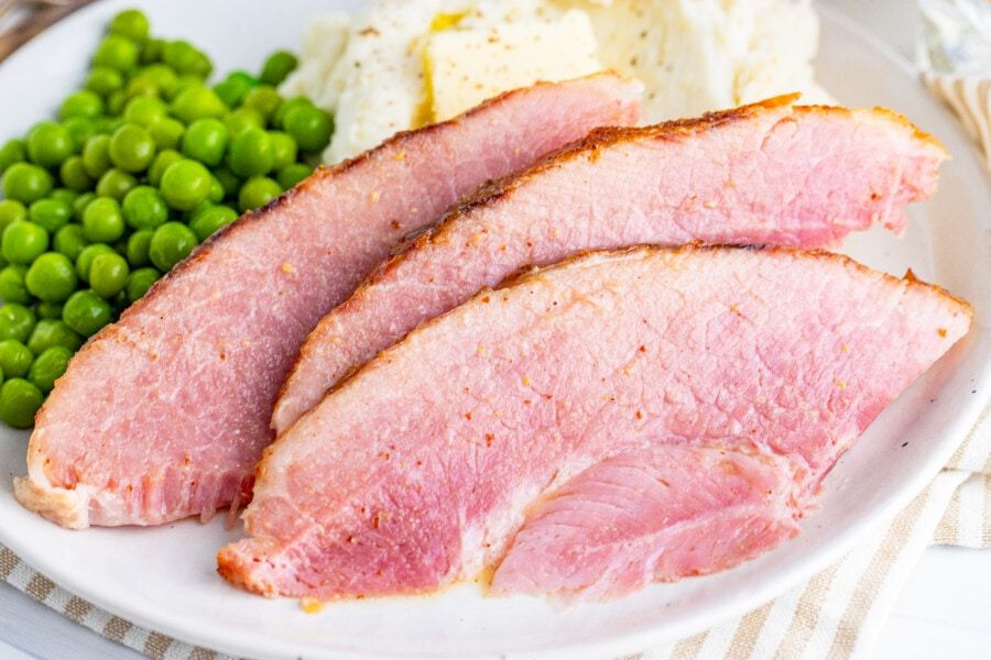 Closeup shot of sliced ham with mashed potatoes and peas on white plate