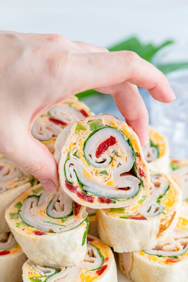 Closeup shot of hand holding a slice of honey mustard turkey wrap above more wraps below