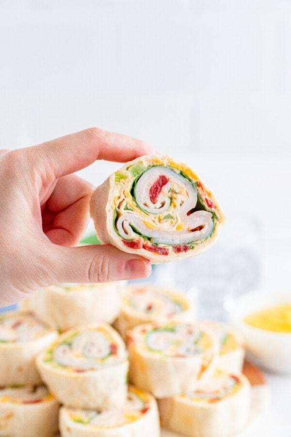 Hand holding honey mustard turkey pinwheels with more hony mustard turkey wrap slices in background