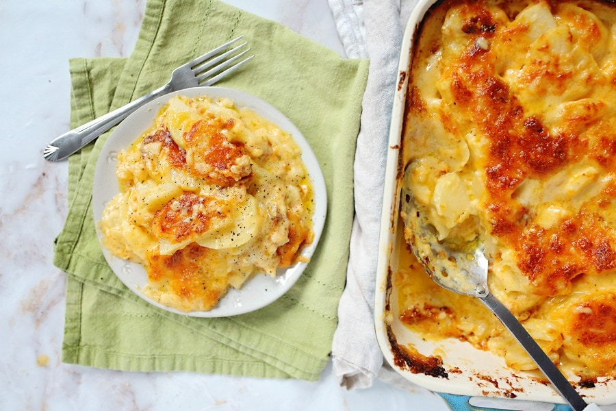 White casserole dish filled with cheesy scalloped potatoes and a plate with a serving of potatoes on it.