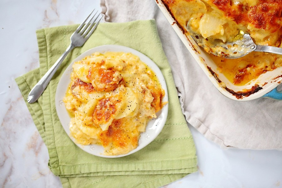 Small plate of cheesy scalloped potatoes with a fork. Part of the casserole dish is visible with some cheesy scalloped potatoes missing.