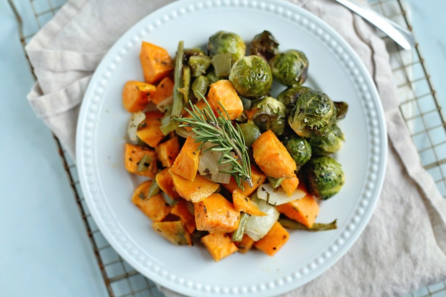 Sweet potatoes and Brussels sprouts on white plate.