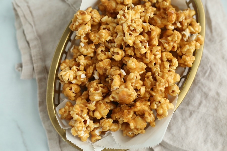 Caramel popcorn in a gold colored oval basket on a dish towel.