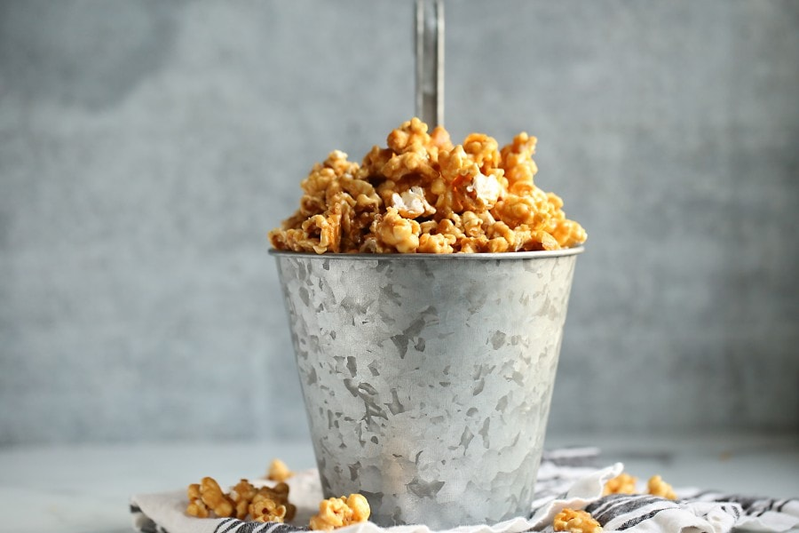 Caramel popcorn overflowing from a tin can with a handle on a dish towel from the side..