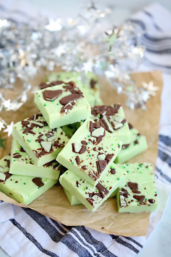 Green Mint fudge piles on a cutting board with chopped chocolate mints on top.