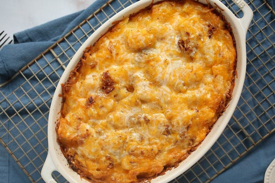 overhead photo of sliced potato casserole with cheese melted on top sitting on a cooling rack