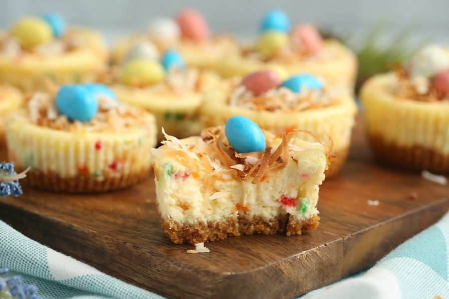 Mini Easter cheesecakes on cutting board with closest cheesecake cut in half
