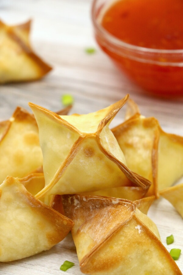 stack of air fryer cream cheese wontons on a counter with sweet chili sauce in the background.