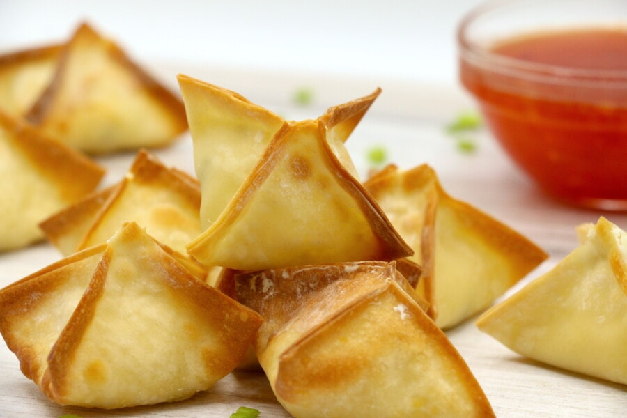 horizontal image of cream cheese wontons stacked in a pyramid shape with a small bowl of sweet chili sauce in the background