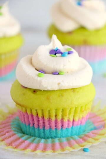 Single Layered Vanilla Cupcake on a white table topped with round sprinkles and white frosting
