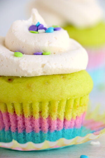 close up image of a rainbow colored layered vanilla cupcake topped with white frosting and sprinkles