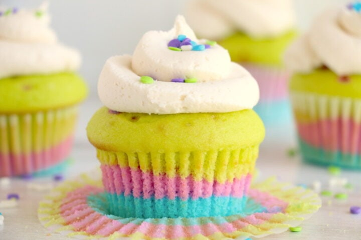 Rainbow Cupcake with paper liner open. Topped with a swirl of frosting and sprinkles.