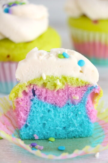rainbow layered vanilla cupcake cut in half to show the inside of the colorful cupcake