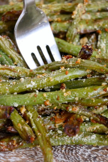 very close up image of air fryer parmesan green beans with a sliver fork